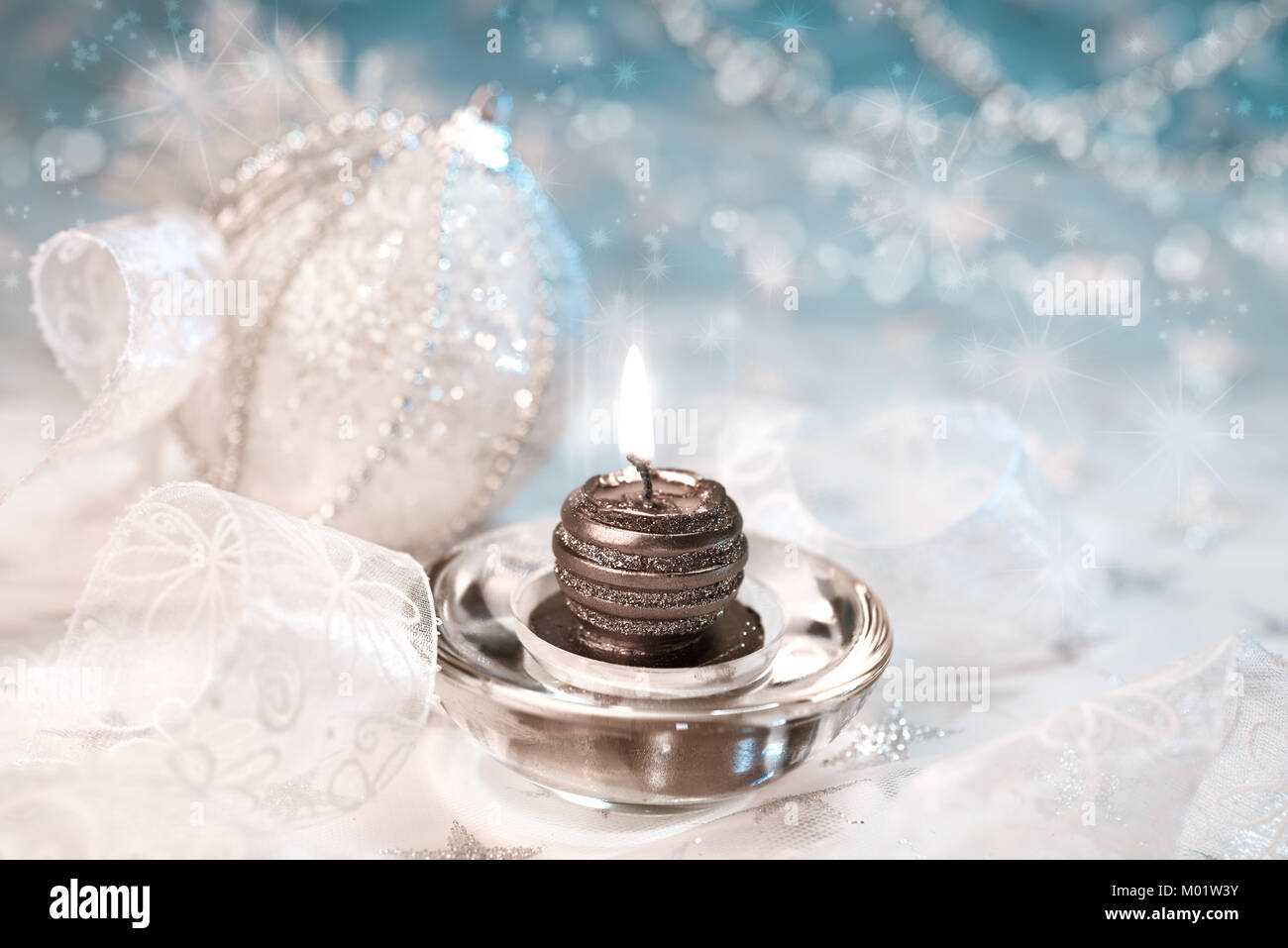 Xmas candle among white and silver decorations Stock Photo