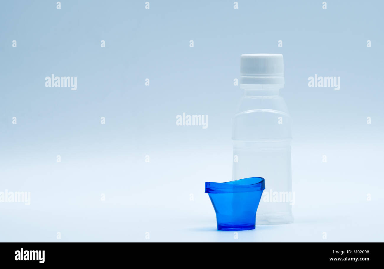 Sterile eye lotion in white plastic bottle with blue eyebath and copy space and blank label. Eye wash after contact - Stock Image