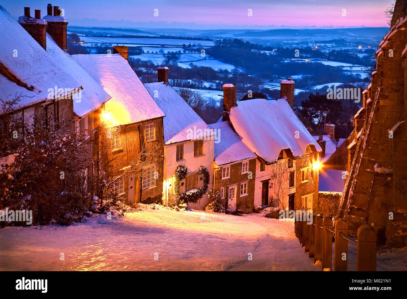 Gold Hill Shaftesbury Dorset after a fall of snow and lit by an evening sunset on a cold January winters evening - Stock Image