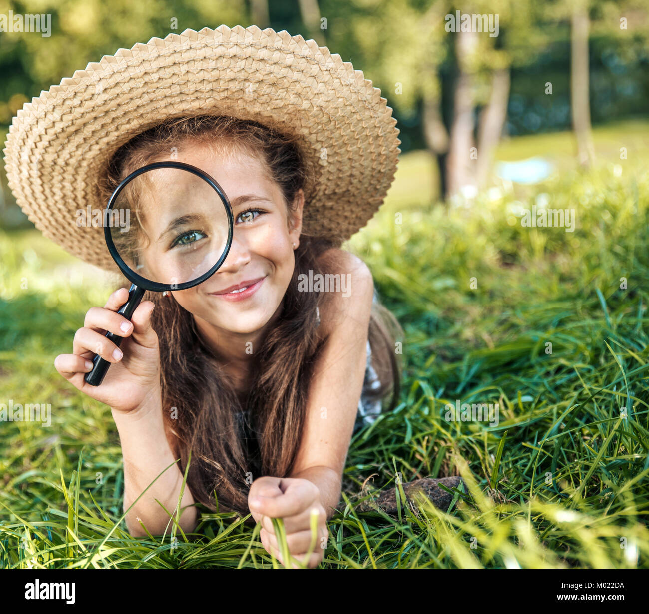 Pretty girl holding a magnifying glass - Stock Image