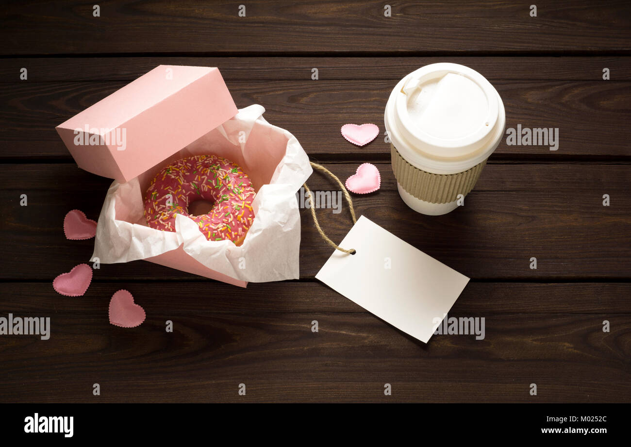 Creative valentine concept photo of donut with take away coffee on wooden background. - Stock Image