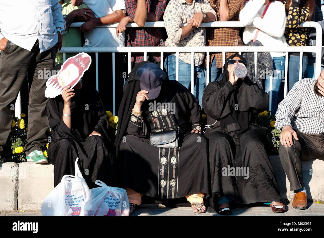 Burka clad women shield themselves from the Qatar sun. - Stock Image