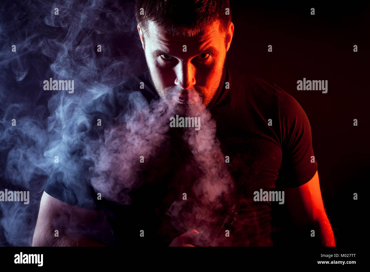 A young stylish male smoker in a black T-shirt stares and exhales from the nose a large cloud of smoke from the - Stock Image