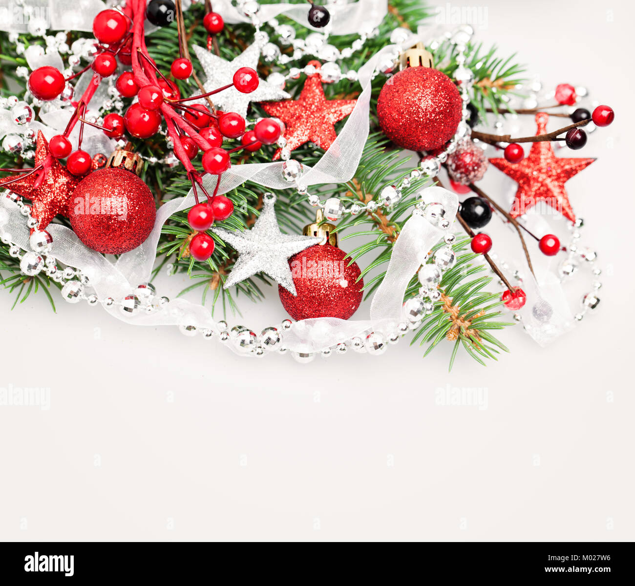 Christmas Background Border with Red Decoration, Xmas Tree Twig, Garland and Xmas Glass Balls - Stock Image