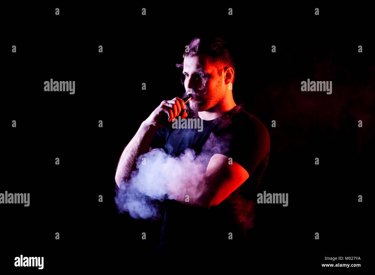 vaping man holding a mod. A cloud of vapor. Black background. - Stock Image