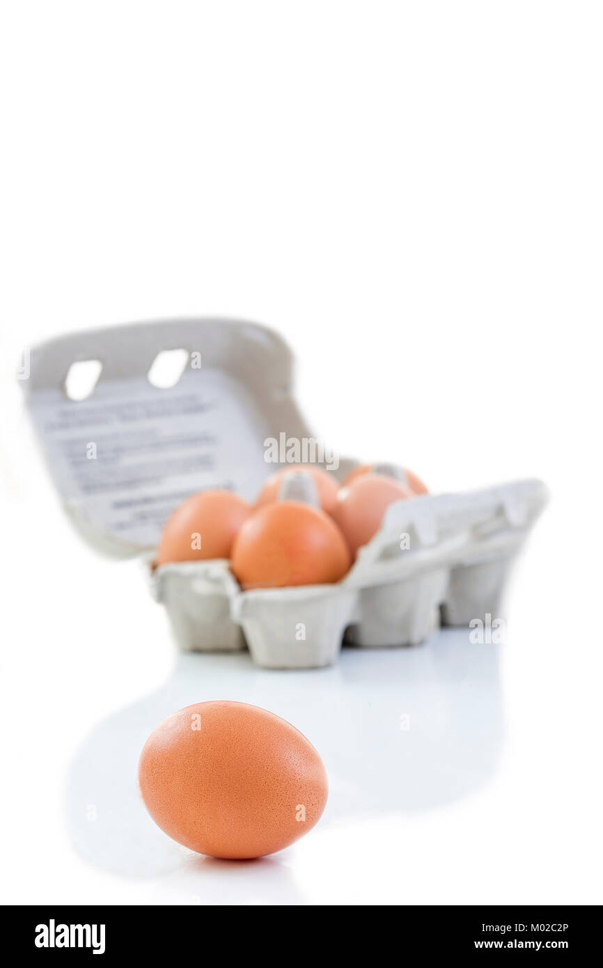 Close up shot of an open recyclable egg carton with 5 eggs inside and one egg next to it on a white background Ecological - Stock Image