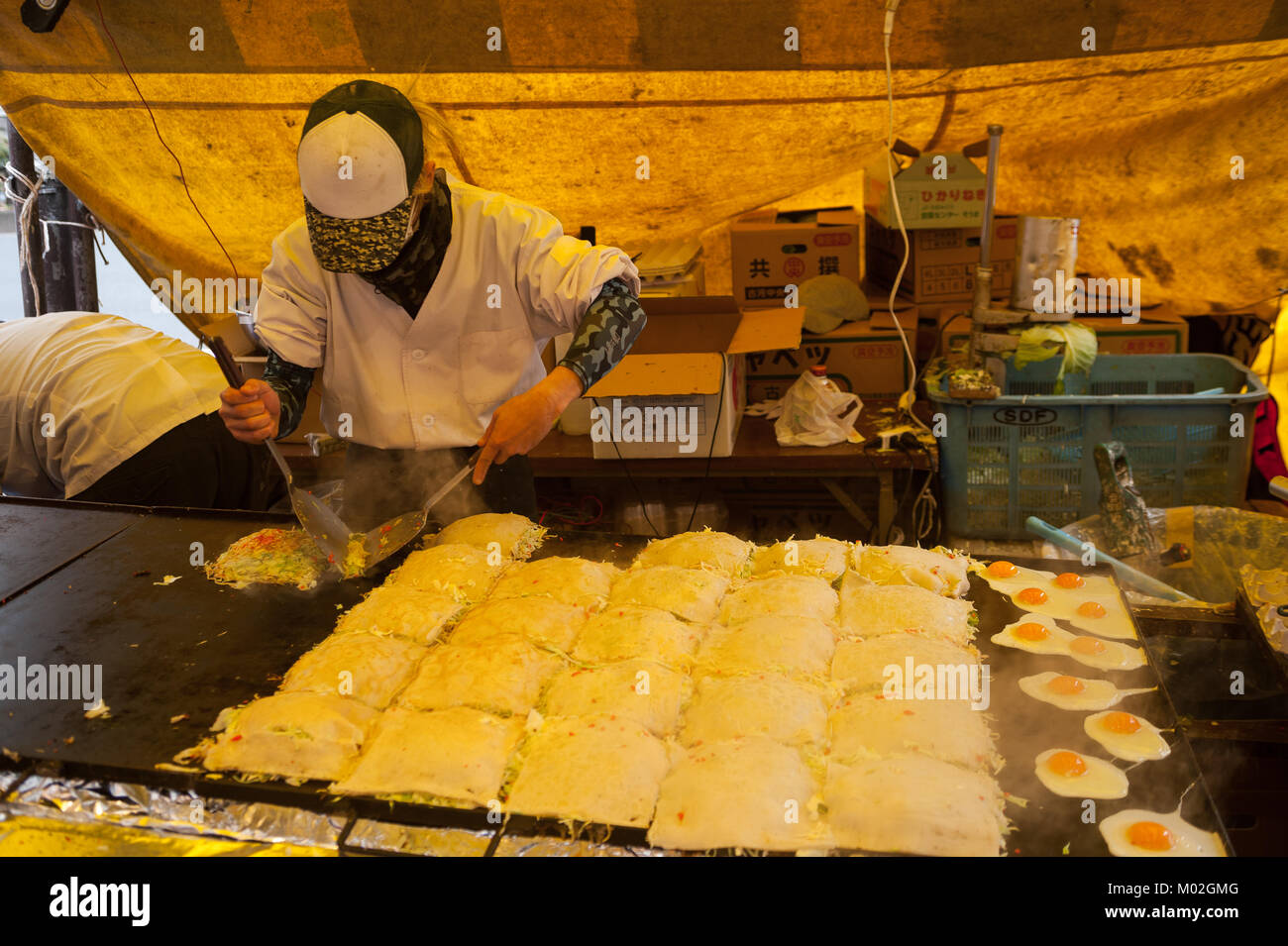 31.12.2017, Tokyo, Japan, Asia - A man prepares freshly roasted pancakes at a street stall in Tokyo's city district - Stock Image