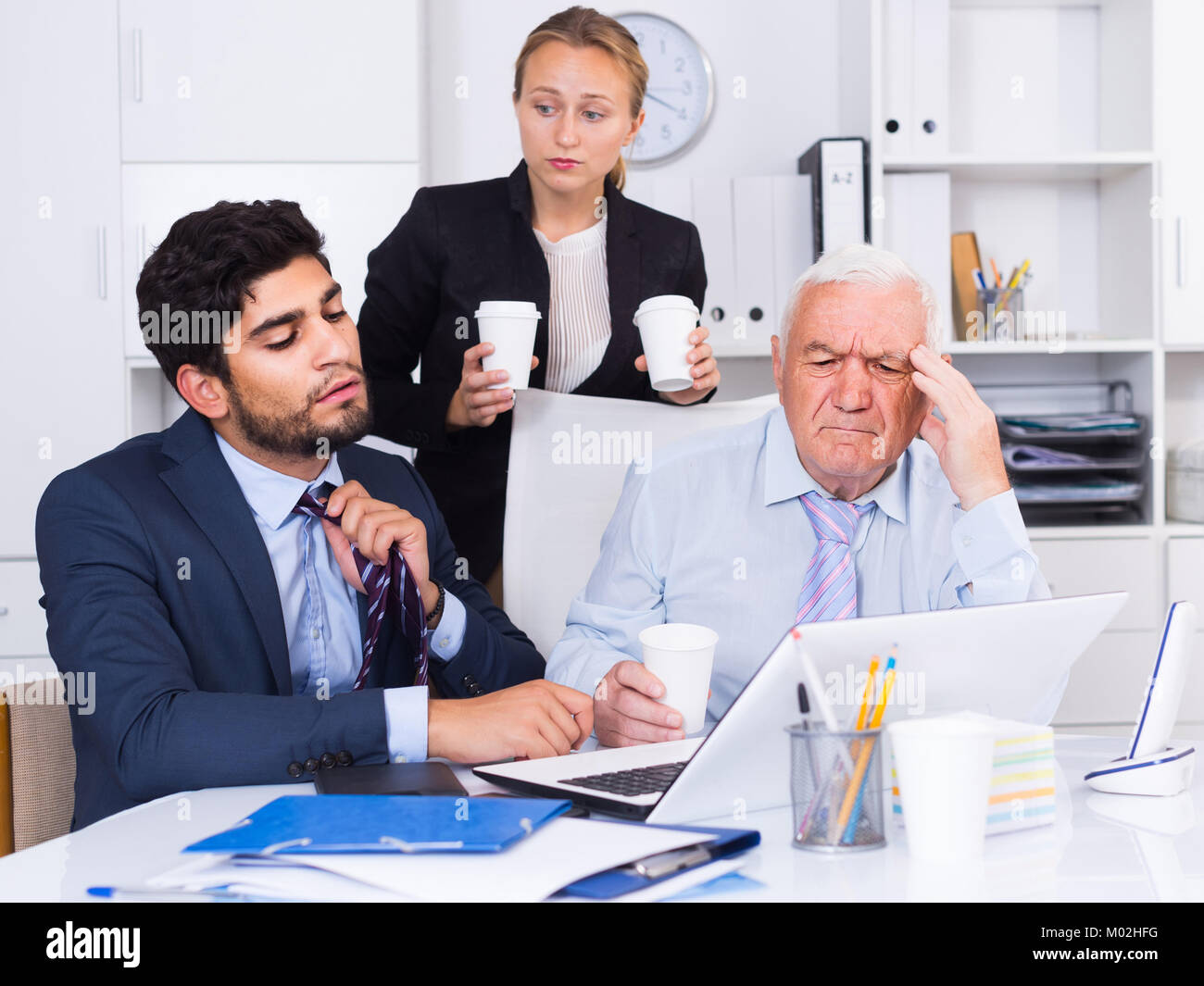 Mature man is having complicated issue with reports made by subordinates in office. - Stock Image