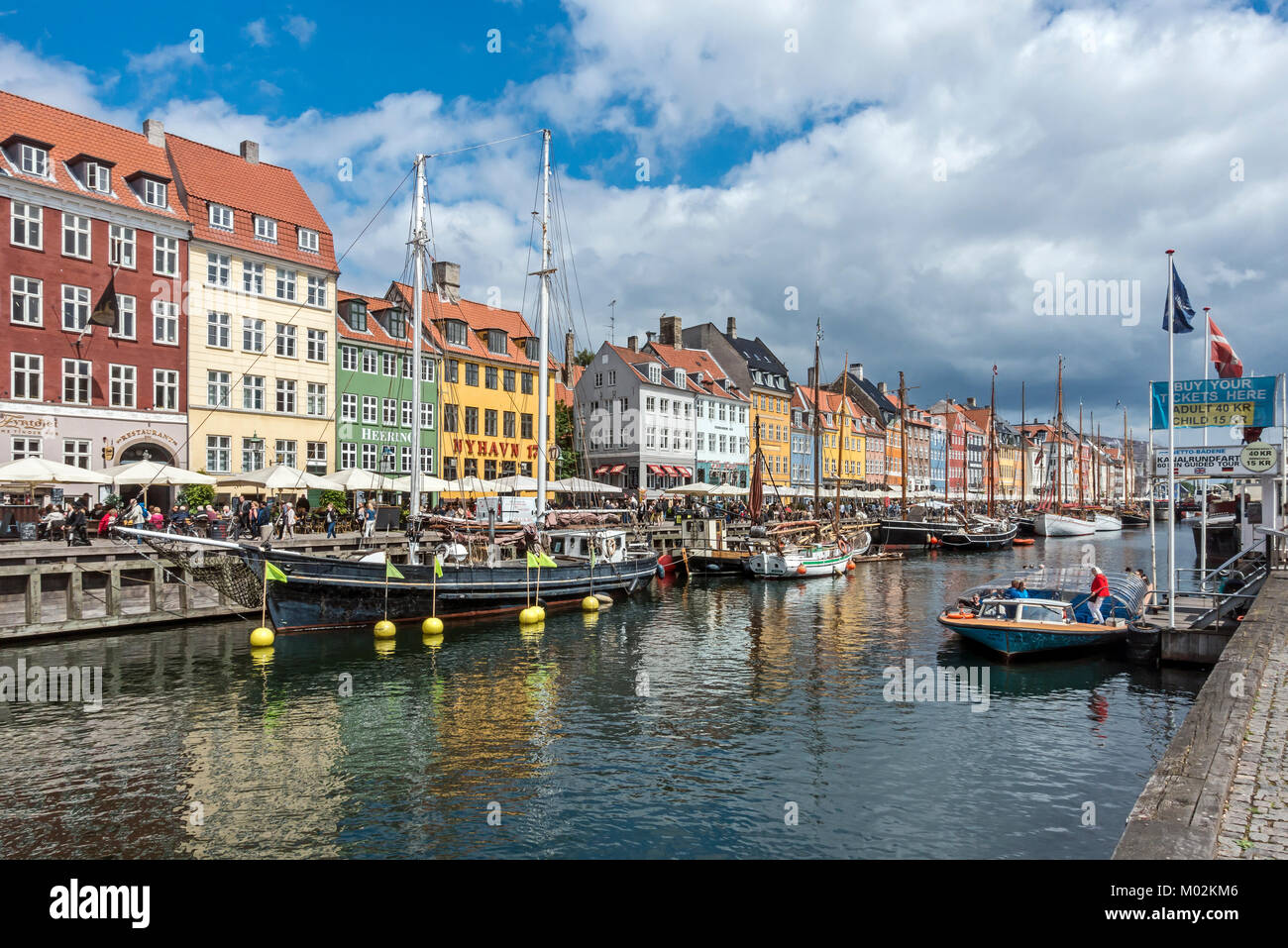 View of Nyhavn in Copenhagen Denmark UK looking towards the harbour entrance with canal boat taking on passengers - Stock Image