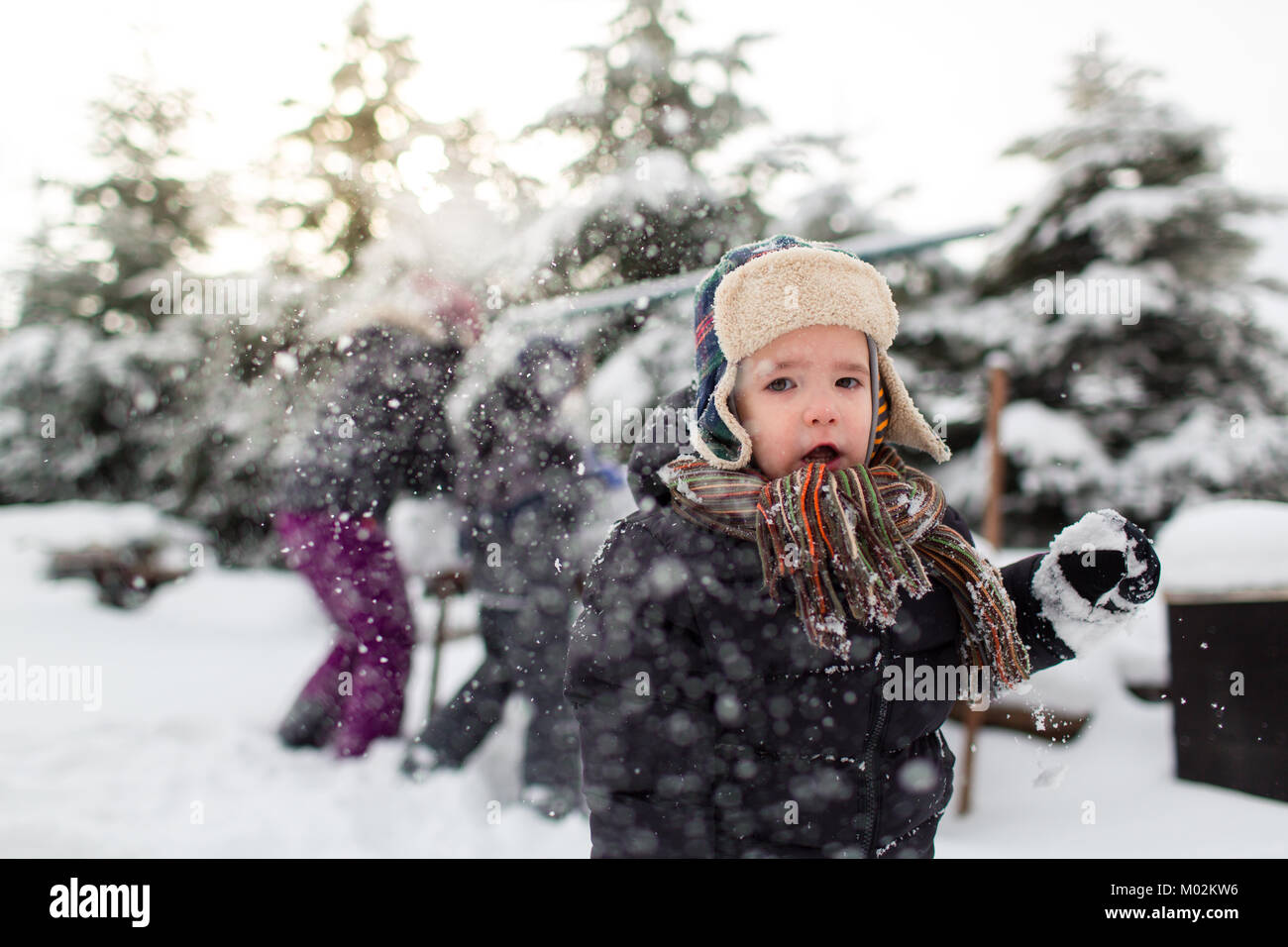 Front view of a little child with open mouth and his family having snowball fight in the background. Family enjoying - Stock Image