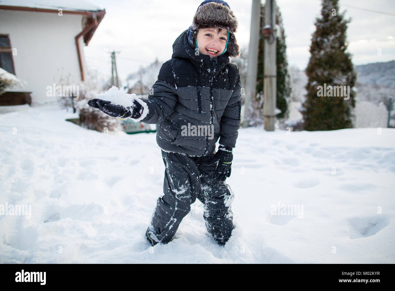 Laughing child in warm clothes having fun during a snowball fight. Boy having fun in the snow. - Stock Image