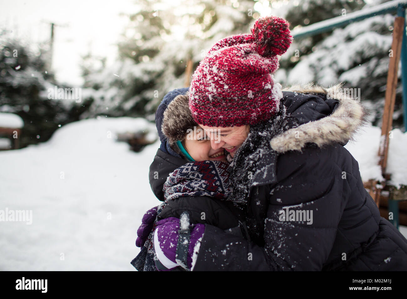 Side view of a happy mother and her son hugging each other after a snowball fight. Family having fun in the snow. - Stock Image