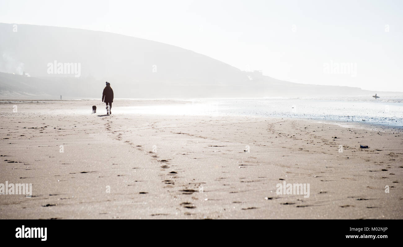 Walking on Croyde Beach with dog in winter - Stock Image