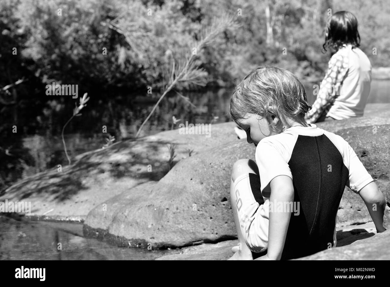 Two children sitting on rocks near a river, Alligator Creek, Bowling Green Bay National Park (Alligator Creek), - Stock Image