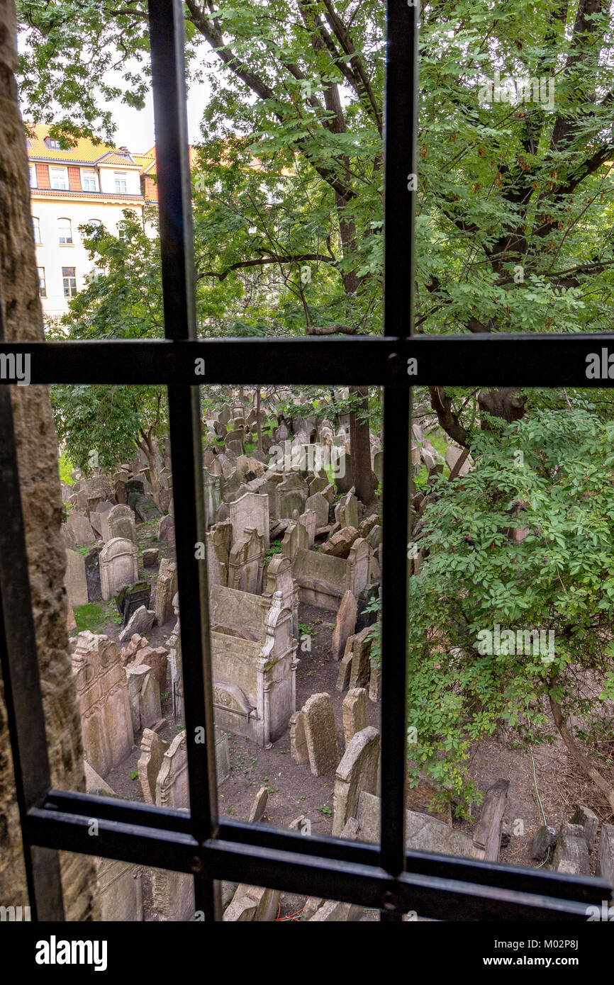 Looking out through a barred window at thousands of crooked tombstones in the Old Jewish Cemetery , Prague, Czech - Stock Image