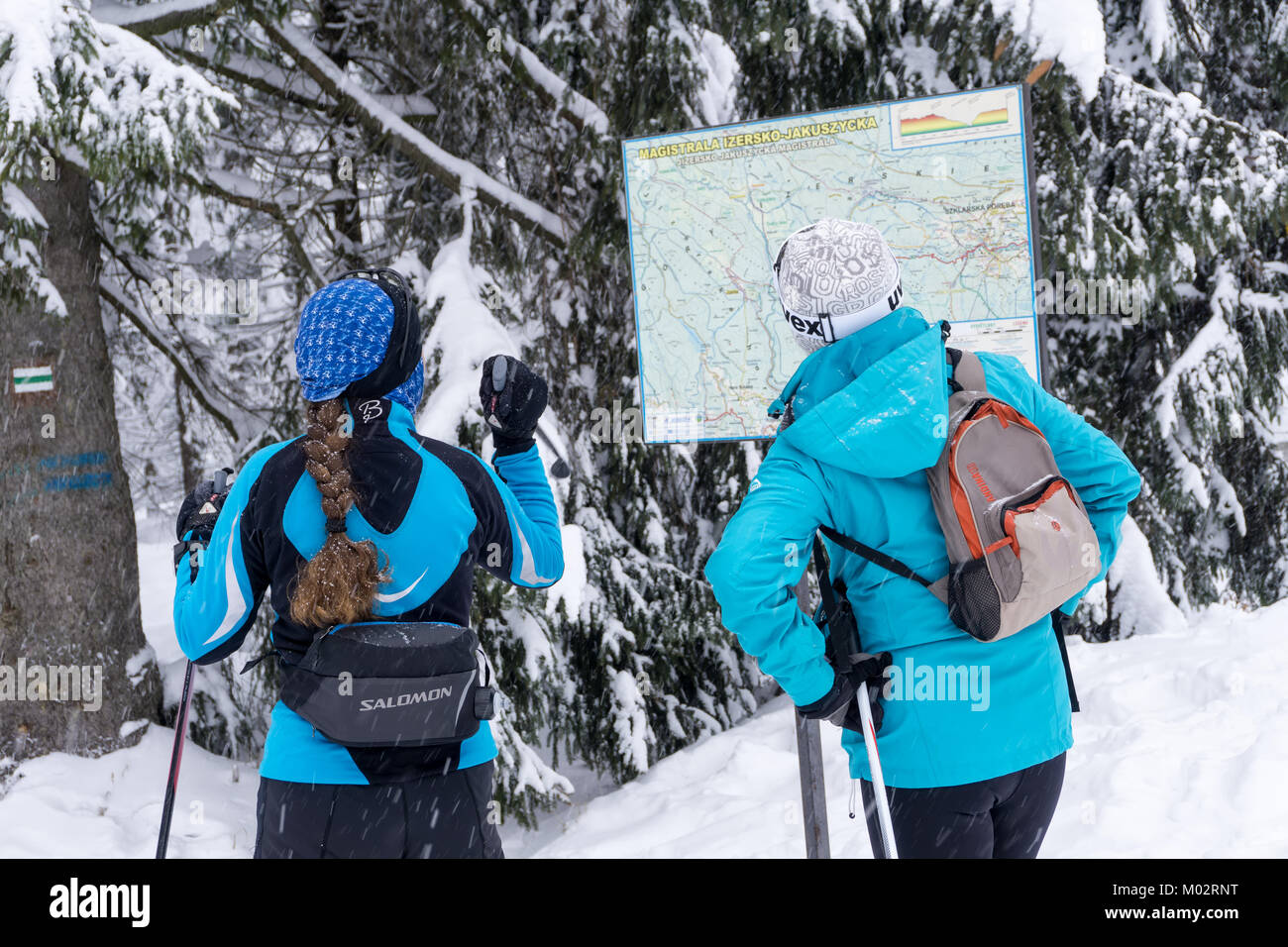 Two women skiers looking for a cross-country route on the map. Jakuszyce, Giant Mountains, Karkonosze, Poland, Europe. - Stock Image