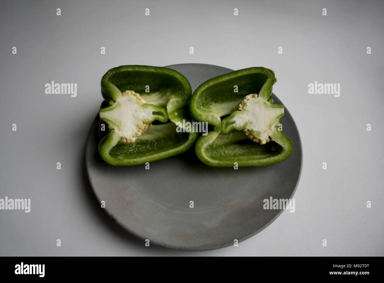 Green poblano pepper halves isolated on grey concrete plate Stock Photo