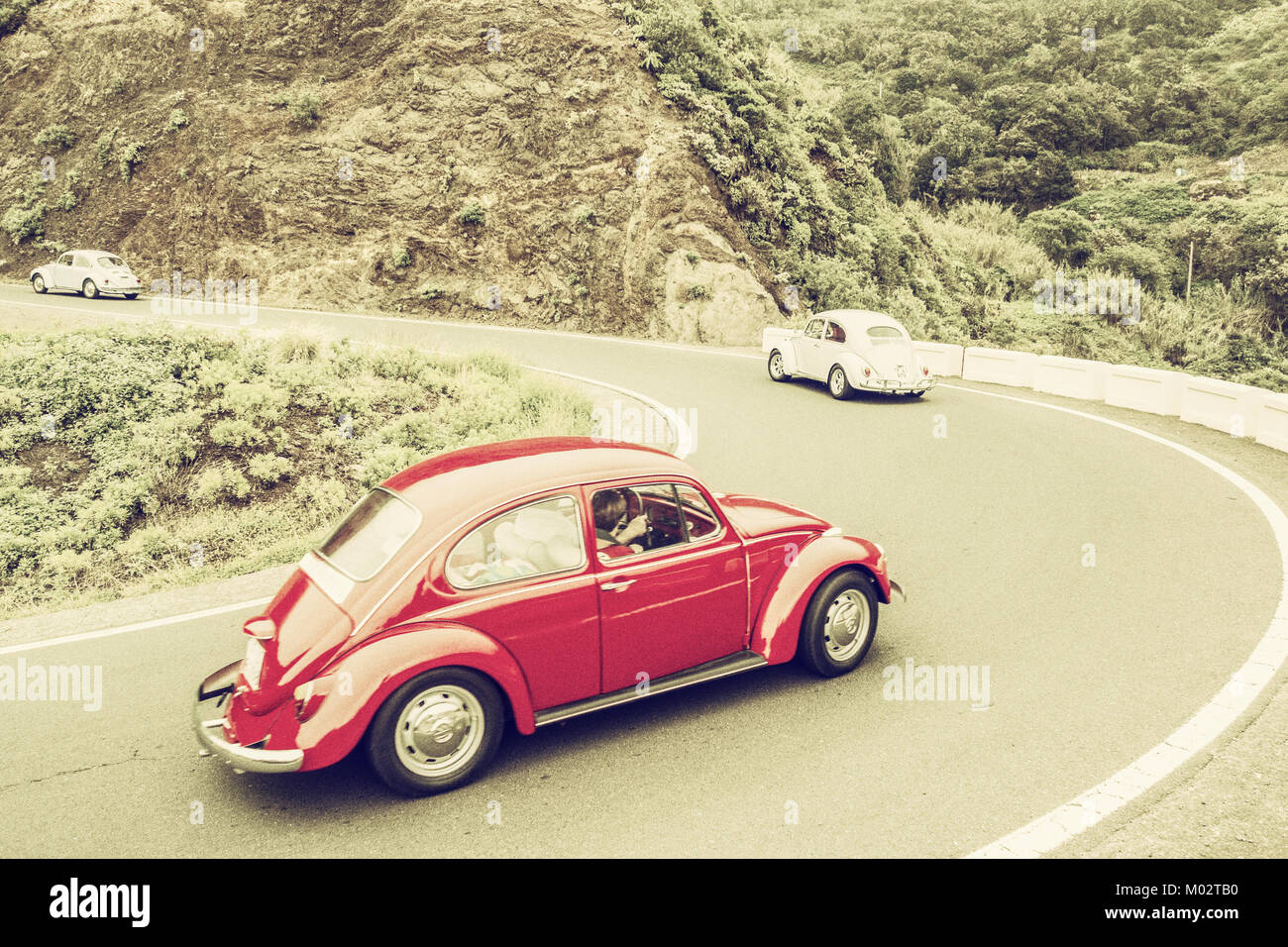 Retro, vintage processing of Volkswagen Beetle on mountain road. Stock Photo