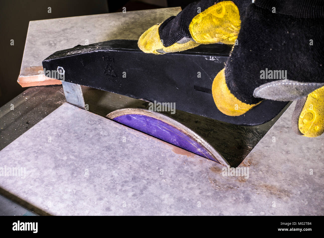 Hand in protective glove, holding the safety guard above the cutting disc of a water cooled ceramic tile cutter, - Stock Image