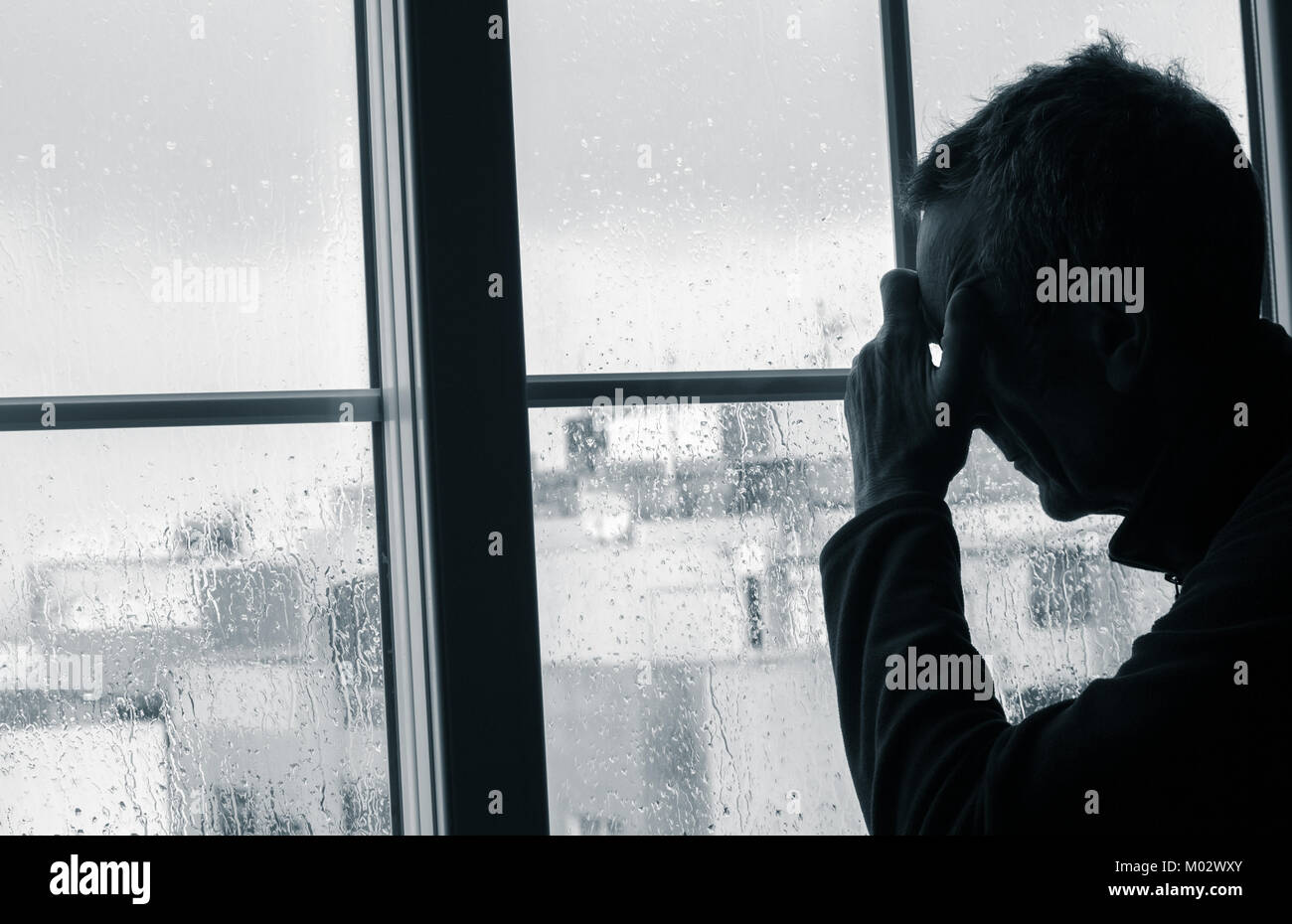 Mature man with hand on head near window on a rainy day. Concept image for depression, male depression, mental health, - Stock Image