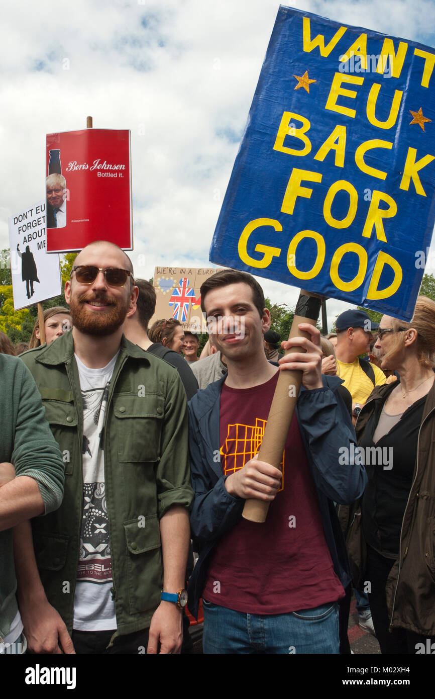 Young man with friends holding placard 'Want EU back for good' on march against Brexit. London. - Stock Image