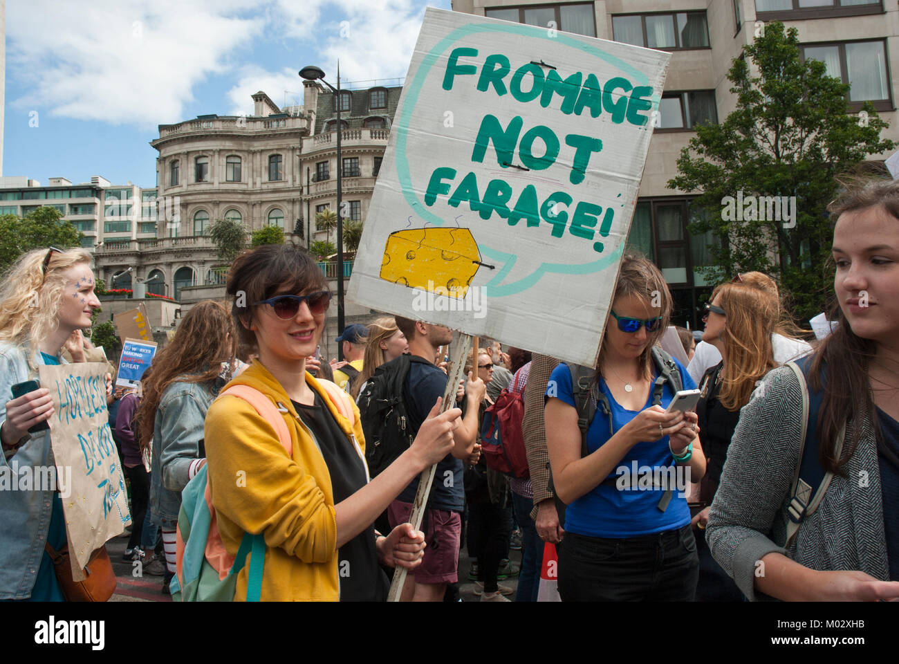 Demonstration against Brexit. Young woman, smiling, holds a placard 'Fromage not Farage' with illustration - Stock Image