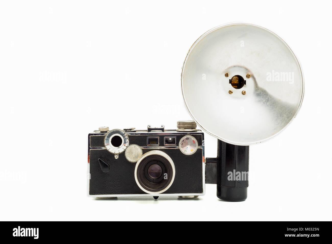 Old 35mm film camera wit flash on white background - Stock Image