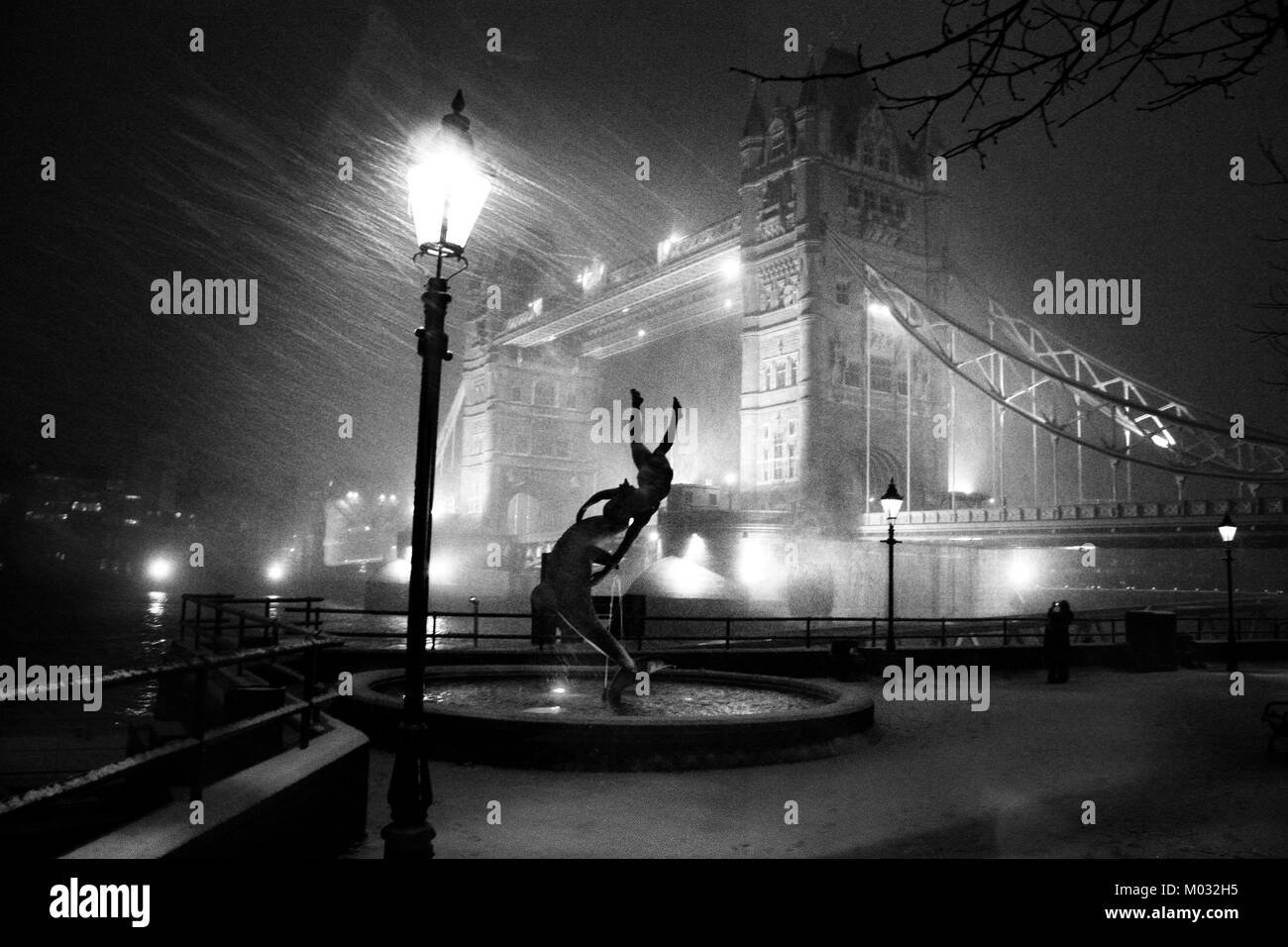 Tower Bridge London in a snow storm at night, black and white with David Wynne sculpture of dolphin and a girl in - Stock Image