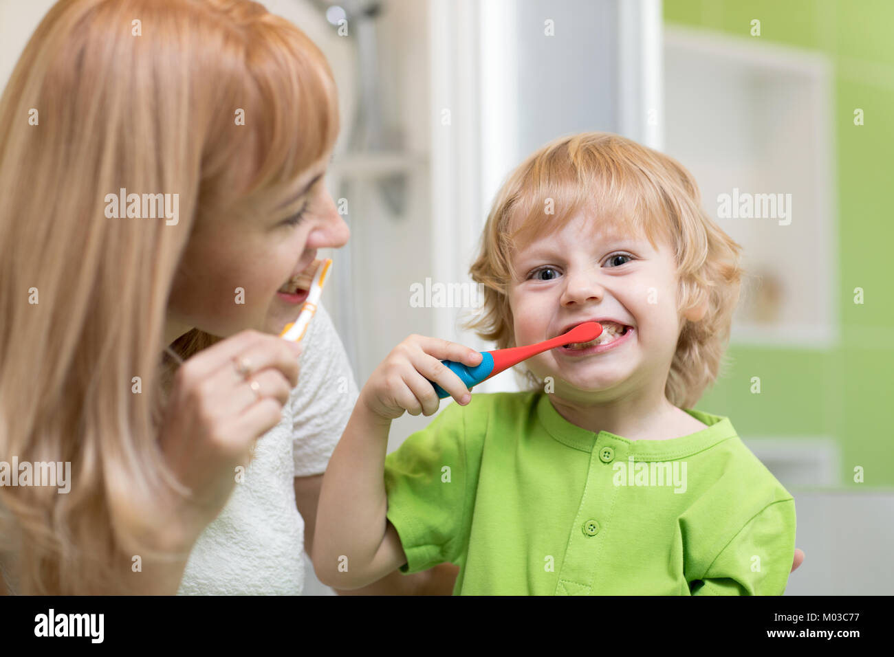 Mother teaches her child son how to brush teeth - Stock Image