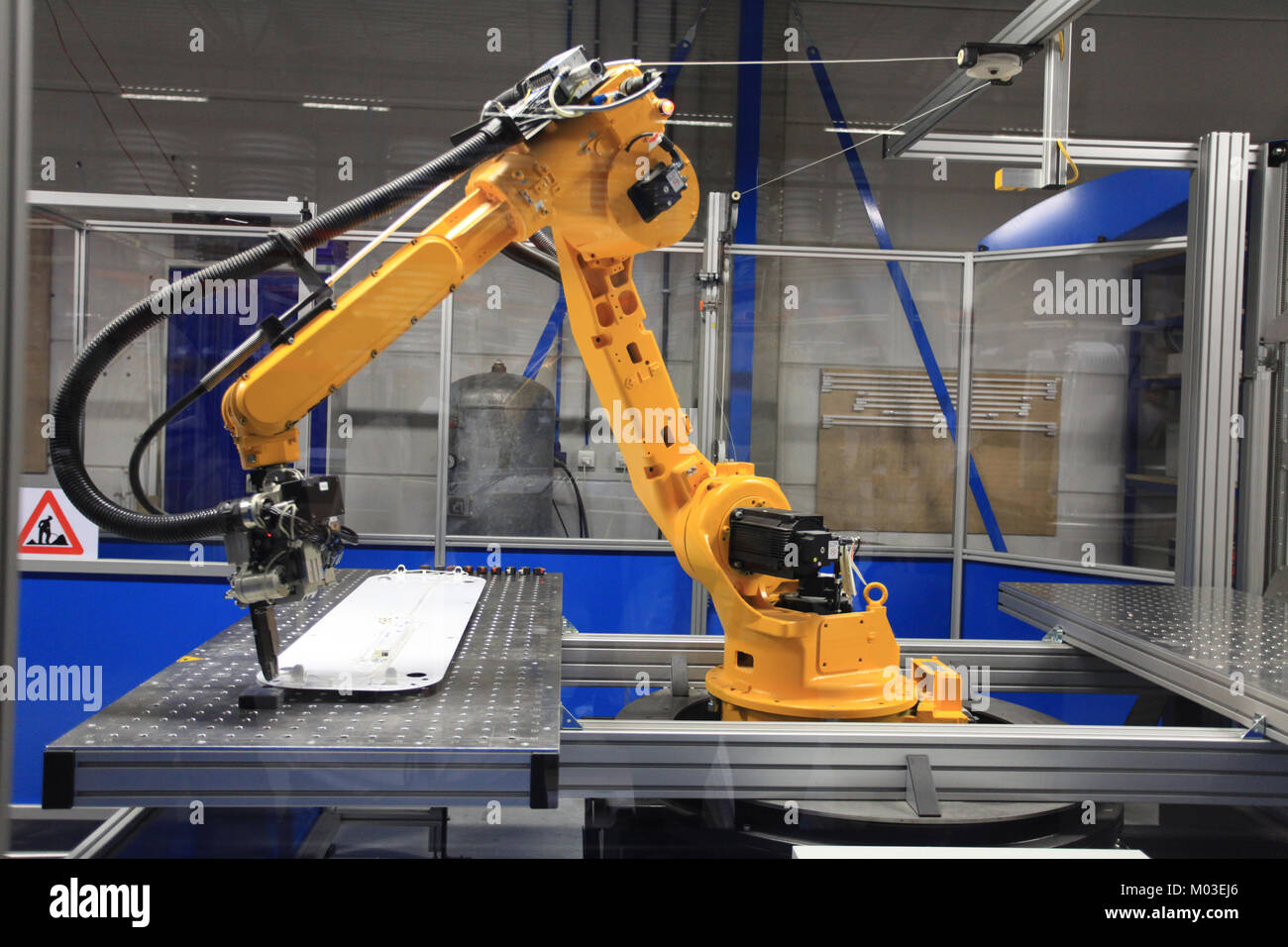 Industrial robotic arm in electronics production line - Stock Image