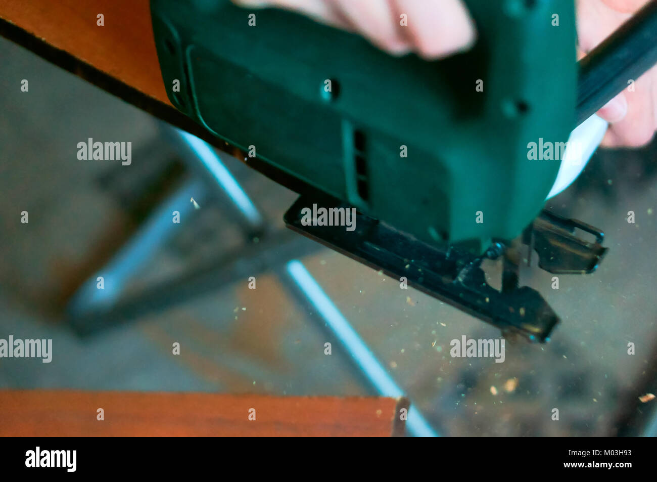 carpenter working with a jig saw and wood cutting jigsaw manual - Stock Image