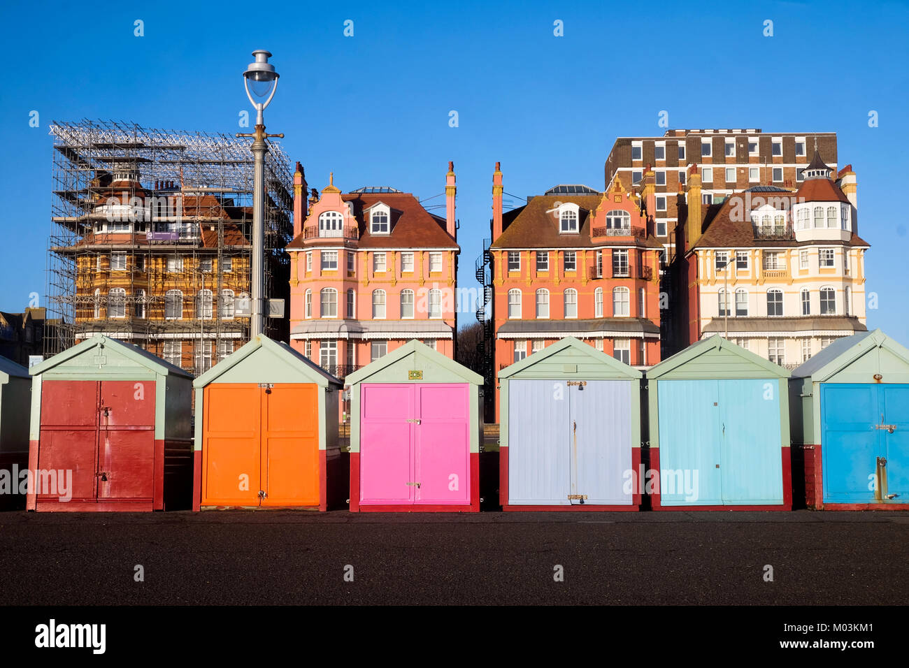 Brighton seafront 7 multi beach huts, behind is blue sky and three very ornate victorian buildings one of the buildings - Stock Image