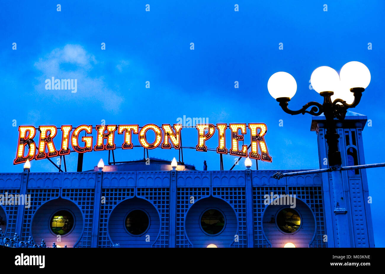 Brighton Pier bright red and yellow neon sign saying Brighton Pier, ontop of Brighton Pier entrance with a street - Stock Image