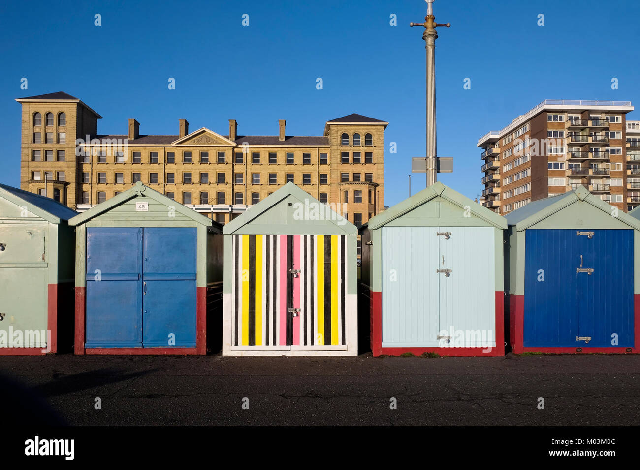 Brighton seafront five beach huts, four with blue and green doors the fifth one in the middle has a multi coloured - Stock Image