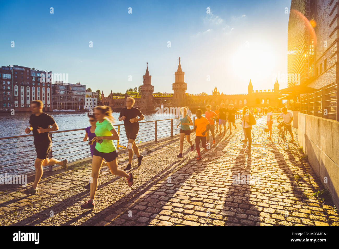 Group of female and male young runners jogging outside in golden evening light at sunset in summer with retro vintage - Stock Image