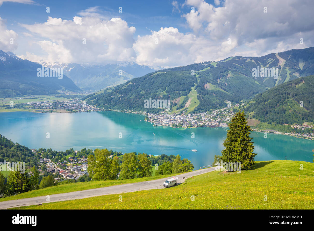 Panoramic View Of Beautiful Scenery In The Alps With Clear Lake And Green Meadows Full Blooming Flowers On A Sunny Day Blue Sky Clouds