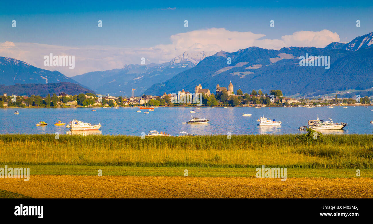 Beautiful view of boats lying in Lake Zurich with the historic town of Rapperswil in the background in golden evening - Stock Image