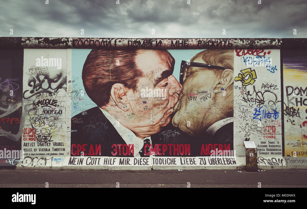 Street art graffiti painting 'The Kiss' by Dmitri Vrubel at famous East Side Gallery with retro vintage - Stock Image