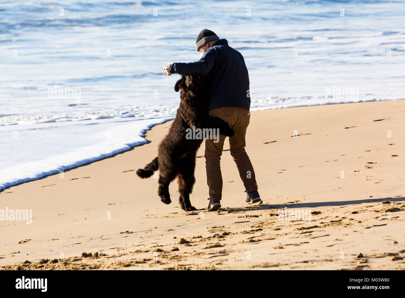 "Bournemouth, Dorset, UK. 18th Jan, 2018. UK weather: a lovely sunny day at Bournemouth beach. Man ""dancing with"" Stock Photo"