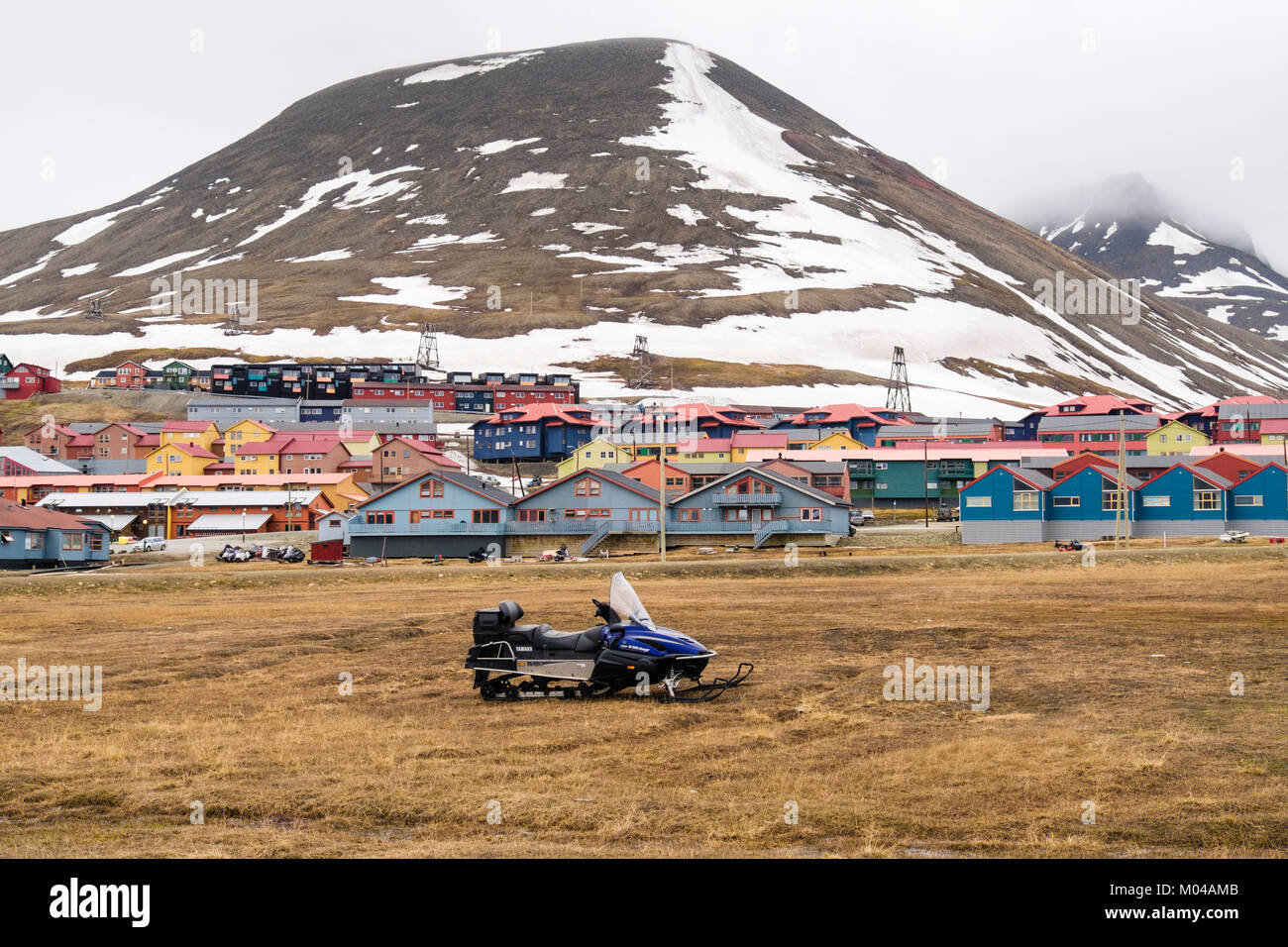 Colourful residential houses with snowmobile scooter parked on grass in old mining town of Longyearbyen, Spitsbergen - Stock Image