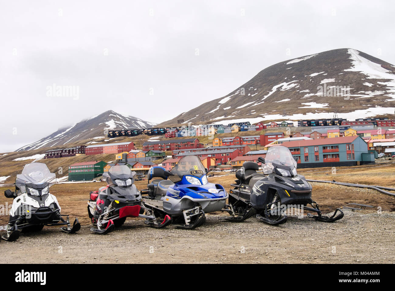 Motorised snowmobile scooters parked on roadside in summer in old mining town of Longyearbyen, Spitsbergen Island, - Stock Image