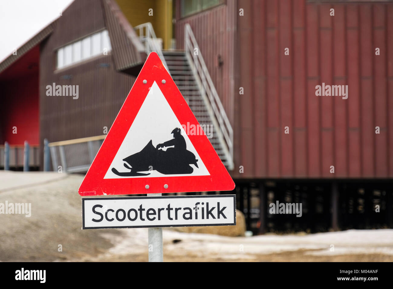 Scootertrafikk red triangle road sign warning of snowmobile scooters. Longyearbyen, Spitsbergen Island, Svalbard, - Stock Image