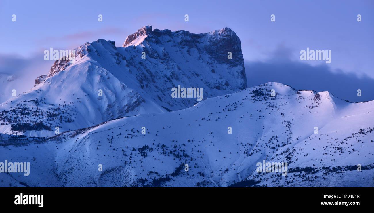 Bure Peak (Pic de Bure) in the Devoluy Mountain range at dusk in Winter. Hautes-Alpes, French Alps, France - Stock Image