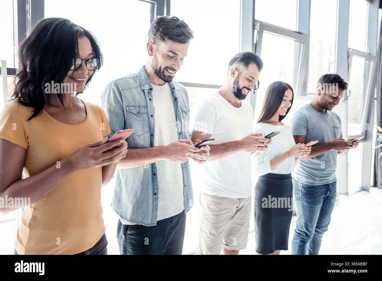 Smiling people using smartphones together - Stock Image