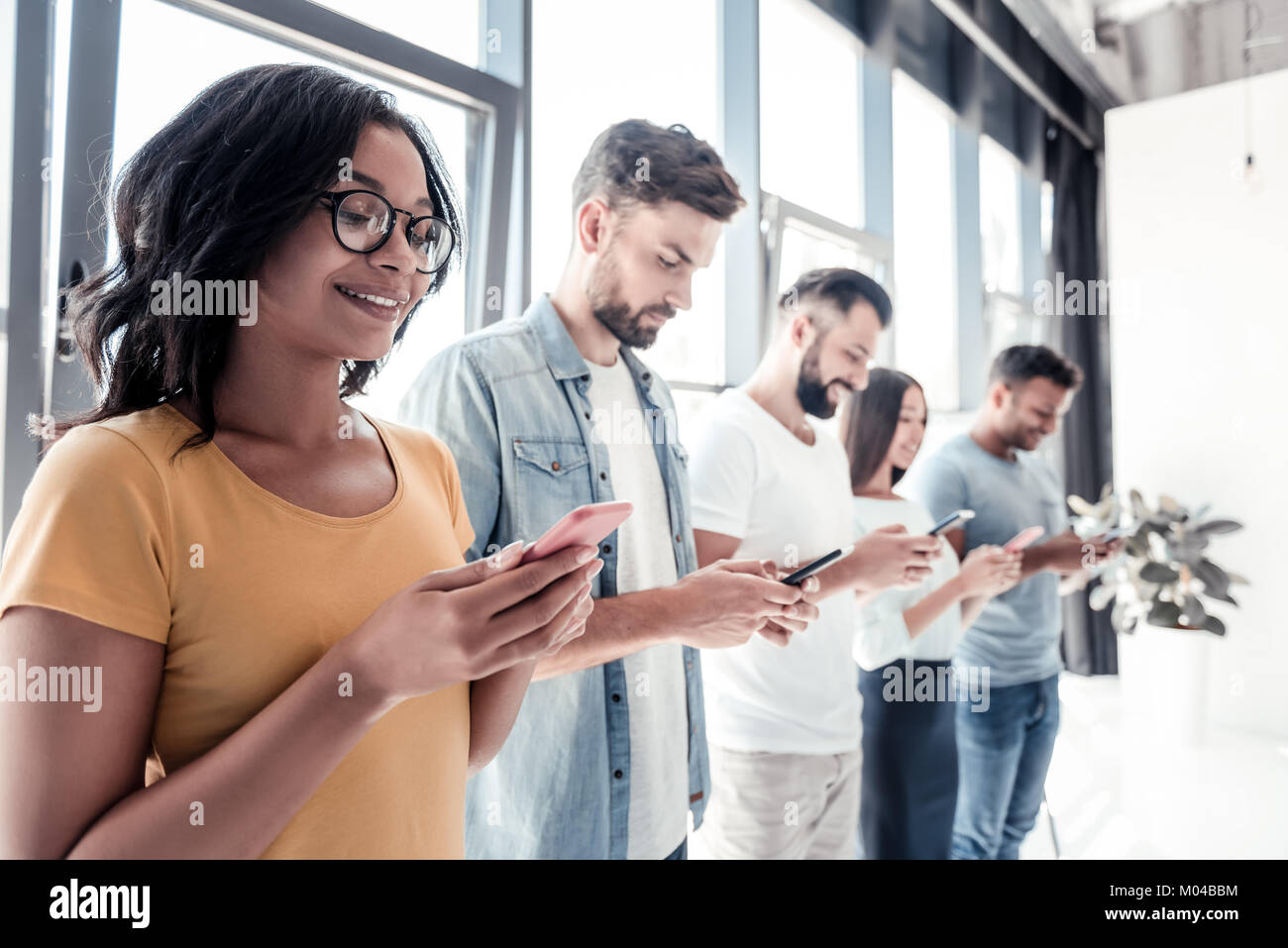 Young lady smiling while looking at smartphone - Stock Image