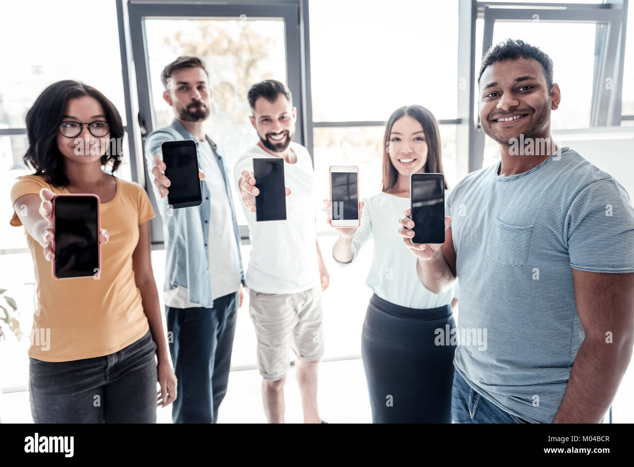 Happy millennial people demonstrating their smartphones - Stock Image