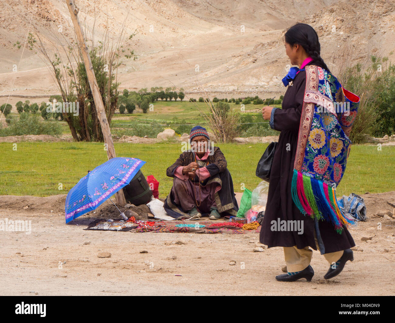 A Buddhist old-age rural woman peddler shows her merchandise in the market and a passerby buyer lady - Stock Image