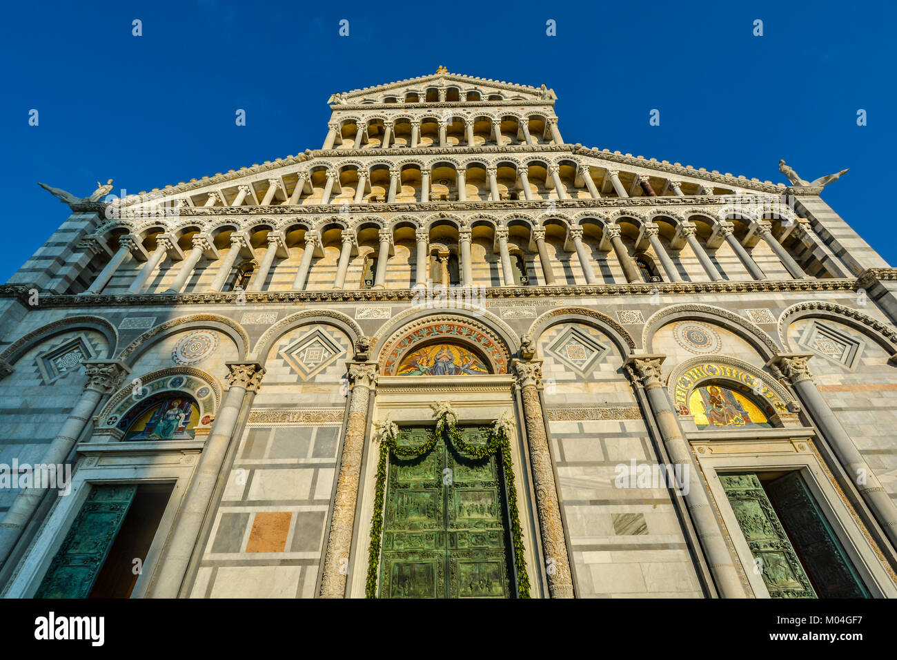 The exterior facade including the bronze doors of the Cathedral of Santa Maria Assunta, the Duomo of Pisa Italy - Stock Image