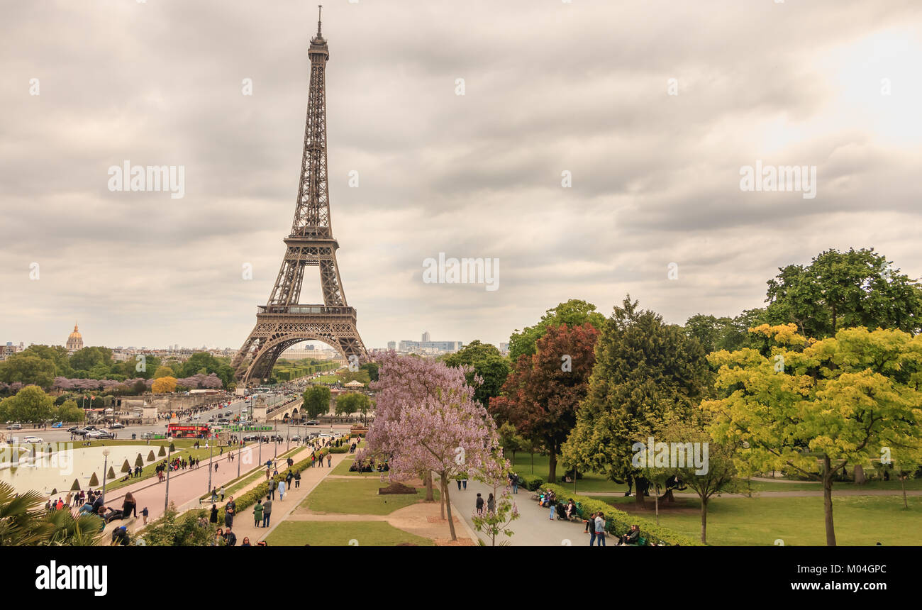 PARIS, FRANCE - May 08, 2017 : wide shot of the Eiffel Tower in Paris with tourists walking in bad weather on a - Stock Image