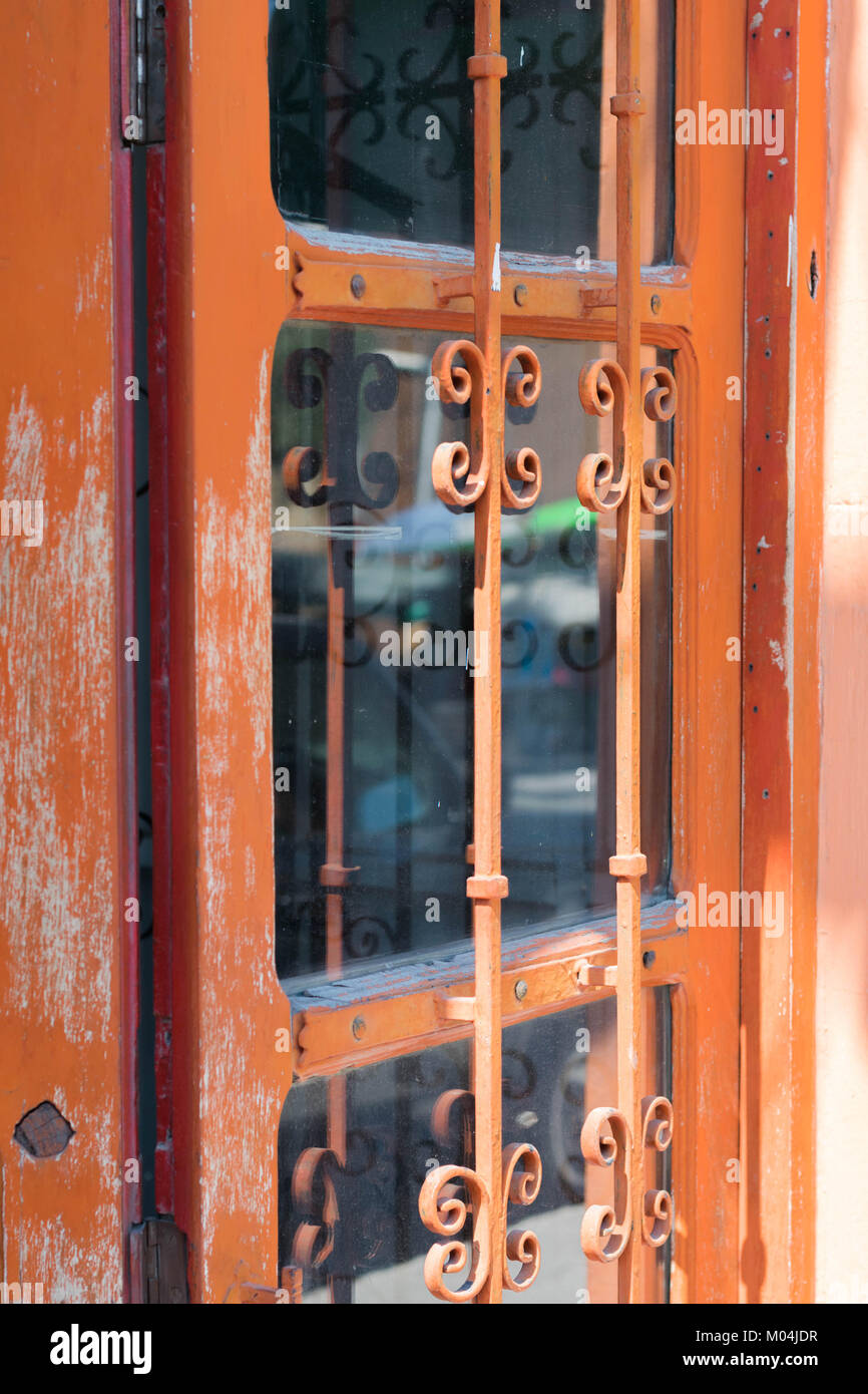 Isolated, close-up of a aged orange metal door, with decorative iron bars and large glass panels, in Mexico - Stock Image